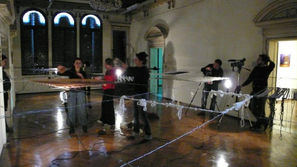 salone principale di palazzetto tito con l'installazione di Maja Bajevic composta da un reticolo di filo di ferro e donne che tessono la lana