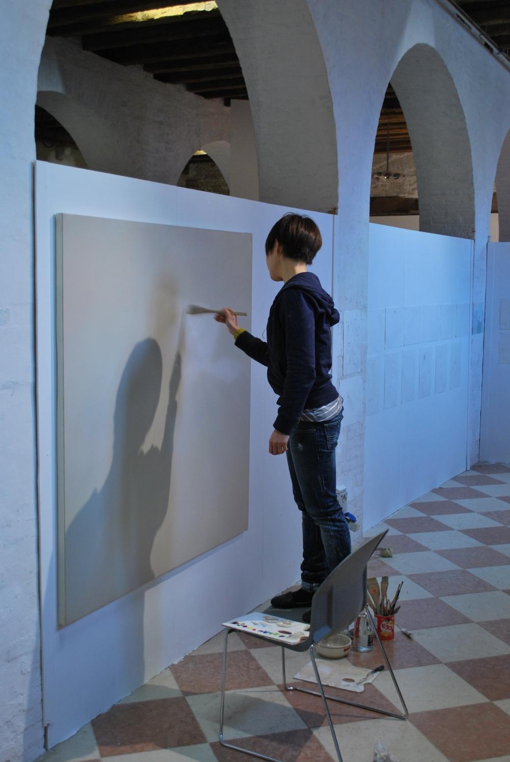 Ayano Yamamoto dipinge nel suo studio stando in piedi su una sedia