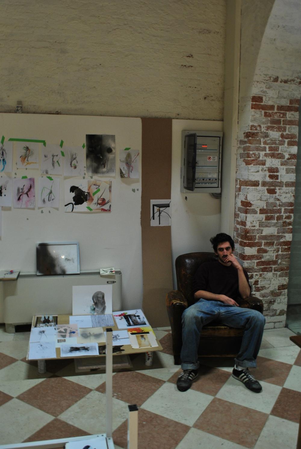 Andrea Kvas è seduto nel suo studio tra i suoi disegni