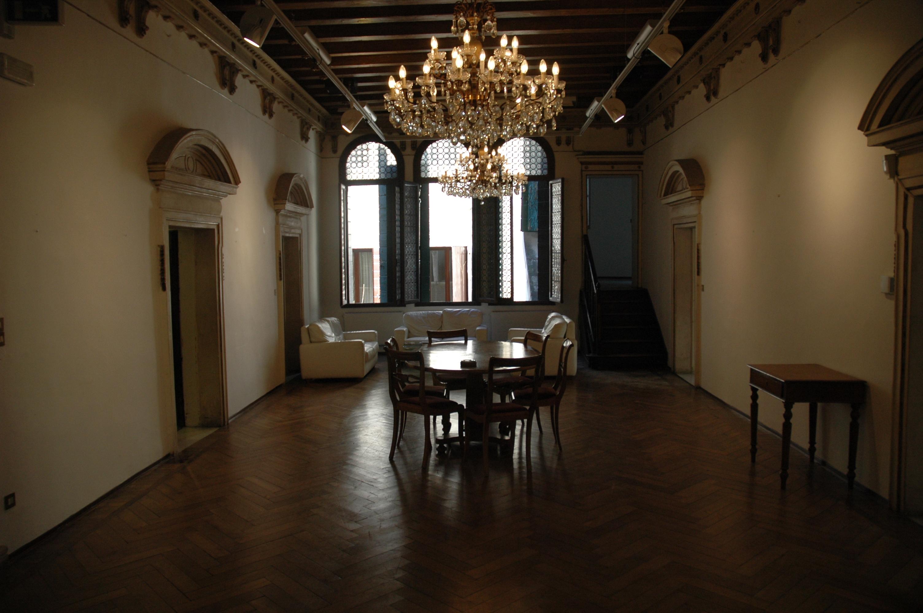 salone di palazzetto tito con tavolo ovale al centro e sedie e due grandi candelabbri a soffritto