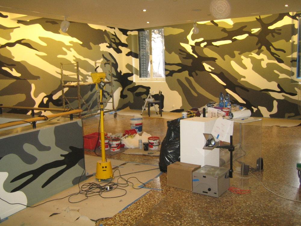primo piano della galleria in fase di allestimento con le pareti dipinte a camouflage