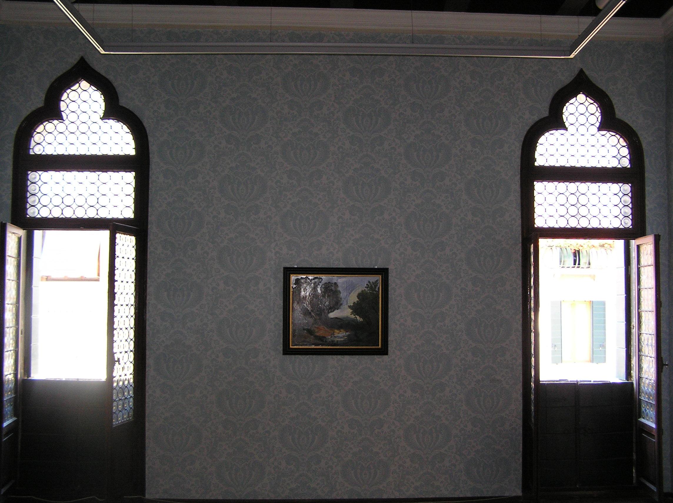 sala di palazzetto tito decorata per una mostra con della carta da parati azzurra a fiori