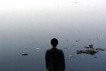 immagine di Kimsooja di spalle che guarda il fiume Yamuna in India