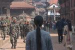 Immagine di Kimsooja di spalle che cammina in una città del Nepal tra civili e militari