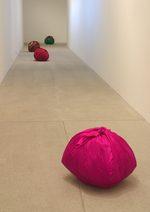 immagine di un corridoio bianco con quattro sacchi di tela colorati contenti indumenti e stracci