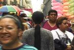 Immagine di Kimsooja di spalle che passeggia nella folla a Città del Messico