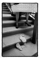 immagine delle gambe di una donna seduta ad un tavolo su una scalinata
