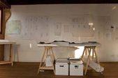 tavolo da lavoro su cavalletti e progetti appesi alle pareti
