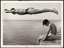 un ragazzo che si tuffa di testa in mare saltando un altro seduto sul bordo di un molo