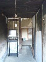 una stanza vuota con una televisione non funzionante e una lampadina che scende dal soffitto