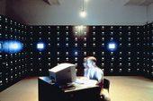 un uomo seduto ad una scrivania davanti ad un pc in una stanza d'archivio