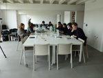 gli artisti degli atelier lavorano attorno ad un tavolo con i loro portatili