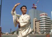 l'artista in posa con il kimono davanti ad un palazzo