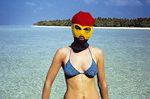 una donna in costume e passamontagna su una spiaggia caraibica