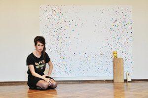 Serena Vestrucci davanti alla sua opera: un foglio con puntini colorati sparsi