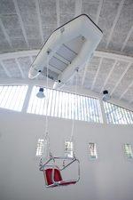 un gommone appeso al contrario su un soffitto da cui scende un seggiolino da luna park