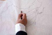 mano che disegna a matita una carta geografica, da uno video in mostra