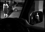 una donna vista da una macchina che si riflette sullo specchietto retrovisore