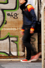 immagine di un ragazzo che cammina davanti ad un graffito disegnato su una saracinesca
