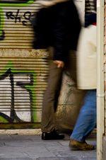 immagine di due persone che camminano davanti ad un graffito su una saracinesca
