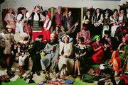 un gruppo di persone in posa in un interno vestiti con costumi tradizionali russi