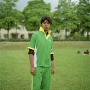 ritratto di un ragazzo immigrato in un parco in divisa da calcio